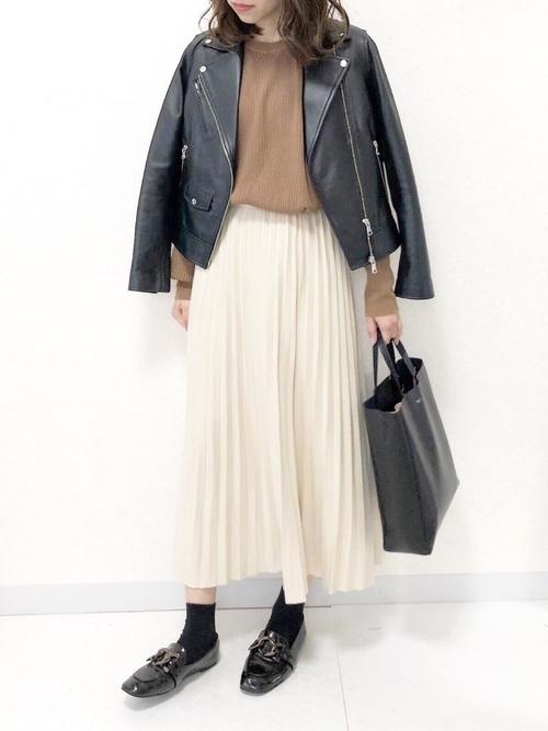 白いプリーツスカートを履いた女性